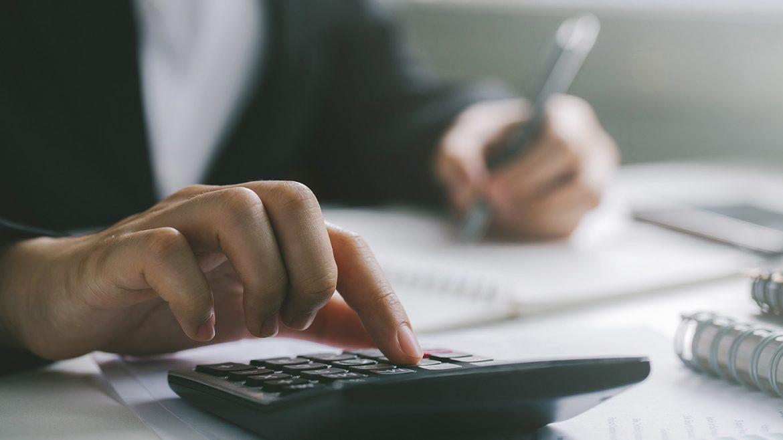 Businessman Writing and Using Calculator